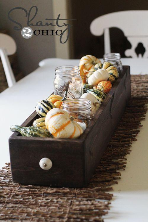 """<p>Mix and match different gourds to fill a DIY statement piece for any dining room table. For an extra rustic touch, add mason jars with candles inside of them. <br></p><p><strong>Get the tutorial at <a href=""""http://www.shanty-2-chic.com/2012/09/fall-table-centerpiece.html"""" rel=""""nofollow noopener"""" target=""""_blank"""" data-ylk=""""slk:Shanty2Chic"""" class=""""link rapid-noclick-resp"""">Shanty2Chic</a>.</strong></p><p><strong><a class=""""link rapid-noclick-resp"""" href=""""https://www.amazon.com/Ball-Mason-Jar-16-Clear-Heritage/dp/B0764L6ZR9/ref=sr_1_3?dchild=1&keywords=mason+jars&qid=1629995256&s=home-garden&sr=1-3&tag=syn-yahoo-20&ascsubtag=%5Bartid%7C10050.g.2130%5Bsrc%7Cyahoo-us"""" rel=""""nofollow noopener"""" target=""""_blank"""" data-ylk=""""slk:SHOP MASON JARS"""">SHOP MASON JARS</a><br></strong></p>"""