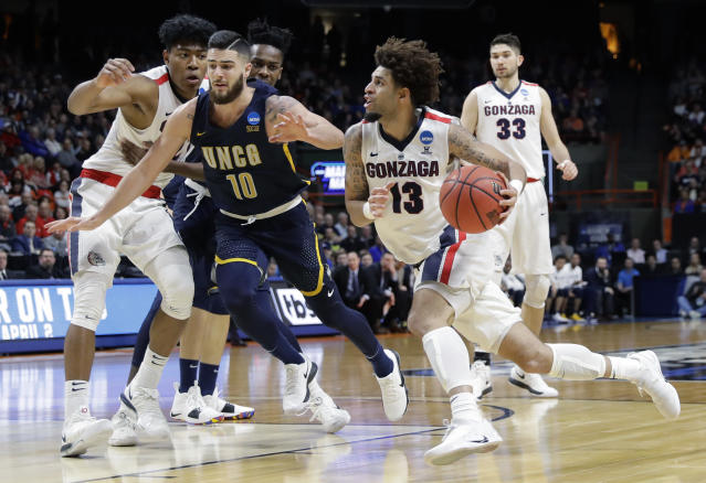 Gonzaga guard Josh Perkins (13) drives against UNC-Greensboro guard Francis Alonso (10) as Gonzaga forward Rui Hachimura looks on at left, during the second half of an NCAA college basketball tournament first-round game, Thursday, March 15, 2018, in Boise, Idaho. (AP Photo/Otto Kitsinger)