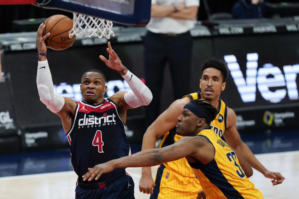 Washington Wizards guard Russell Westbrook (4) shoots past Indiana Pacers center Myles Turner (33) and guard Malcolm Brogdon, back right, during the first half of an NBA basketball game Monday, March 29, 2021, in Washington. (AP Photo/Alex Brandon)