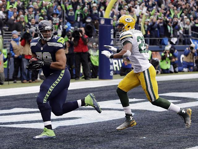 Seattle Seahawks' Garry Gilliam catches a touchdown pass during the second half of the NFL football NFC Championship game against the Green Bay Packers Sunday, Jan. 18, 2015, in Seattle. (AP Photo/David J. Phillip)
