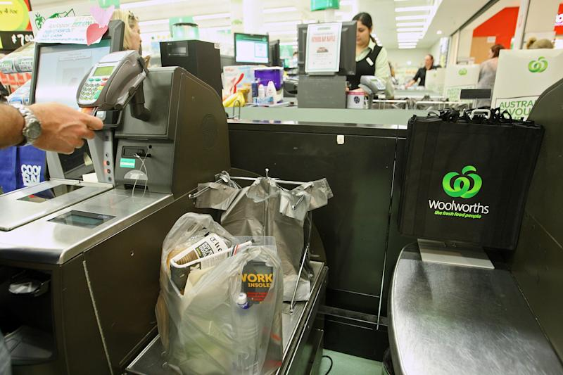 Picture of a Woolworths self-serve checkout, with a customer paying with card at a cash-only register.