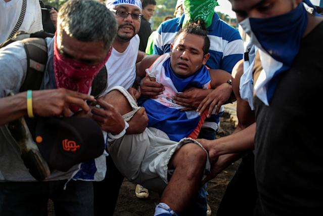 <p>Demonstrators help an injured protester during clashes with riot police during a protest against Nicaragua's President Daniel Ortega's government in Managua, Nicaragua, May 30, 2018. (Photo: Oswaldo Rivas/Reuters) </p>