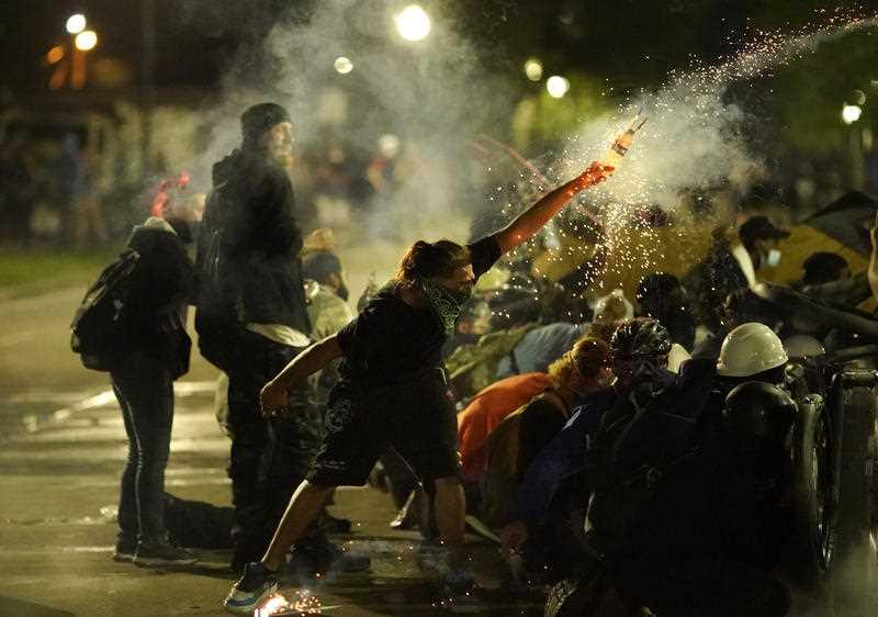 A protester launches a projectile toward police during clashes outside the Kenosha County Courthouse.