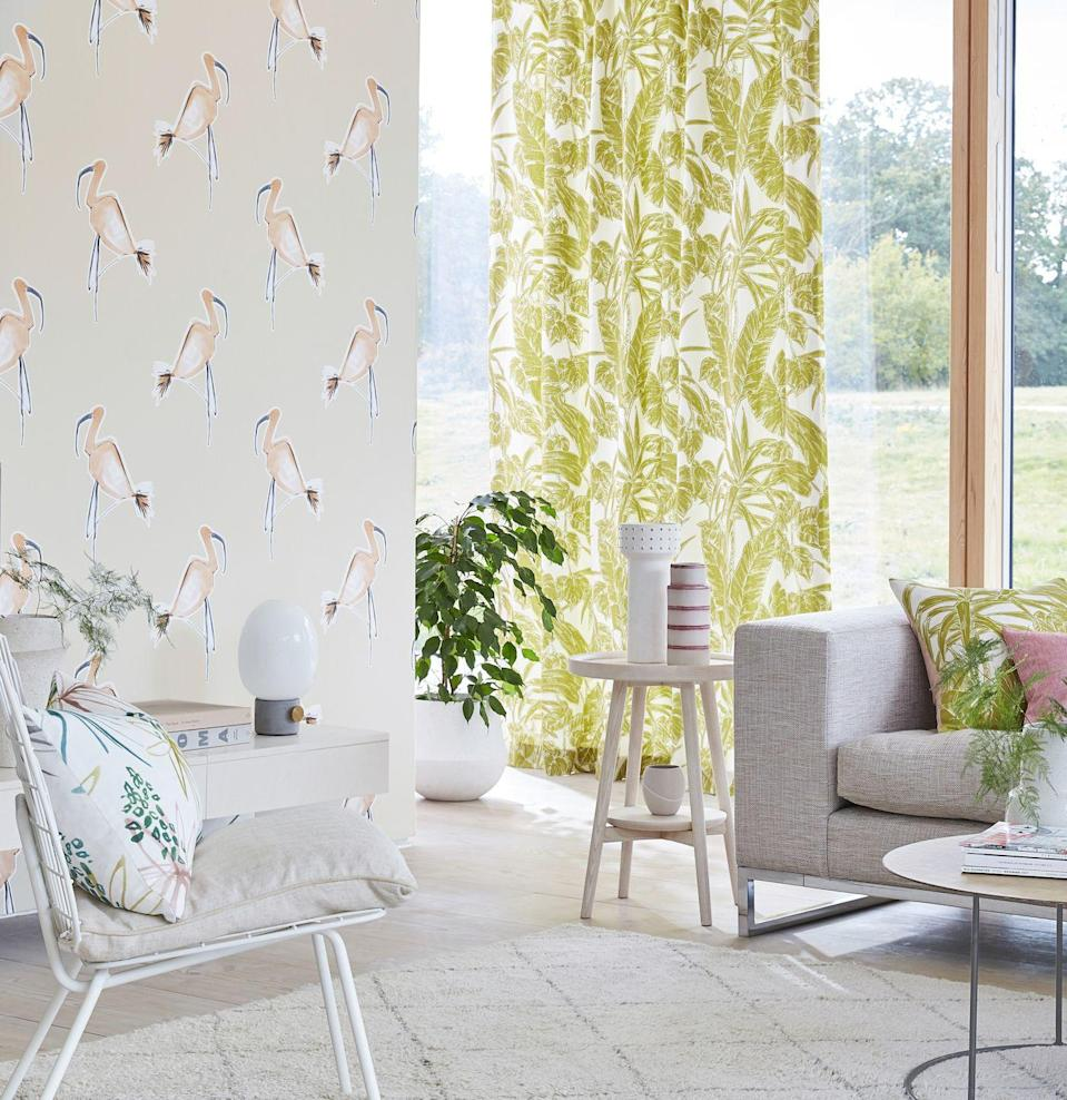 """<p>Another clever living room wallpaper idea is to use it as a partition. In a through room, use wallpaper to define the spaces. This fun but sophisticated flamingo design gives the room a Miami feel, further complemented by the retro-style palm leaf fabric on the <a href=""""https://www.housebeautiful.com/uk/decorate/windows/g35224529/best-blackout-curtains/"""" rel=""""nofollow noopener"""" target=""""_blank"""" data-ylk=""""slk:curtains"""" class=""""link rapid-noclick-resp"""">curtains</a> and the white metal pool chair.</p><p>Pictured: Zanzibar wallpaper; Parlour Palm Citrus Fabric, both <a href=""""https://scion.sandersondesigngroup.com/"""" rel=""""nofollow noopener"""" target=""""_blank"""" data-ylk=""""slk:Scion"""" class=""""link rapid-noclick-resp"""">Scion</a></p>"""