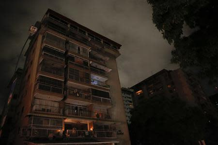 A man stands on the balcony of his apartment as he waits for the power to return after a blackout in Caracas