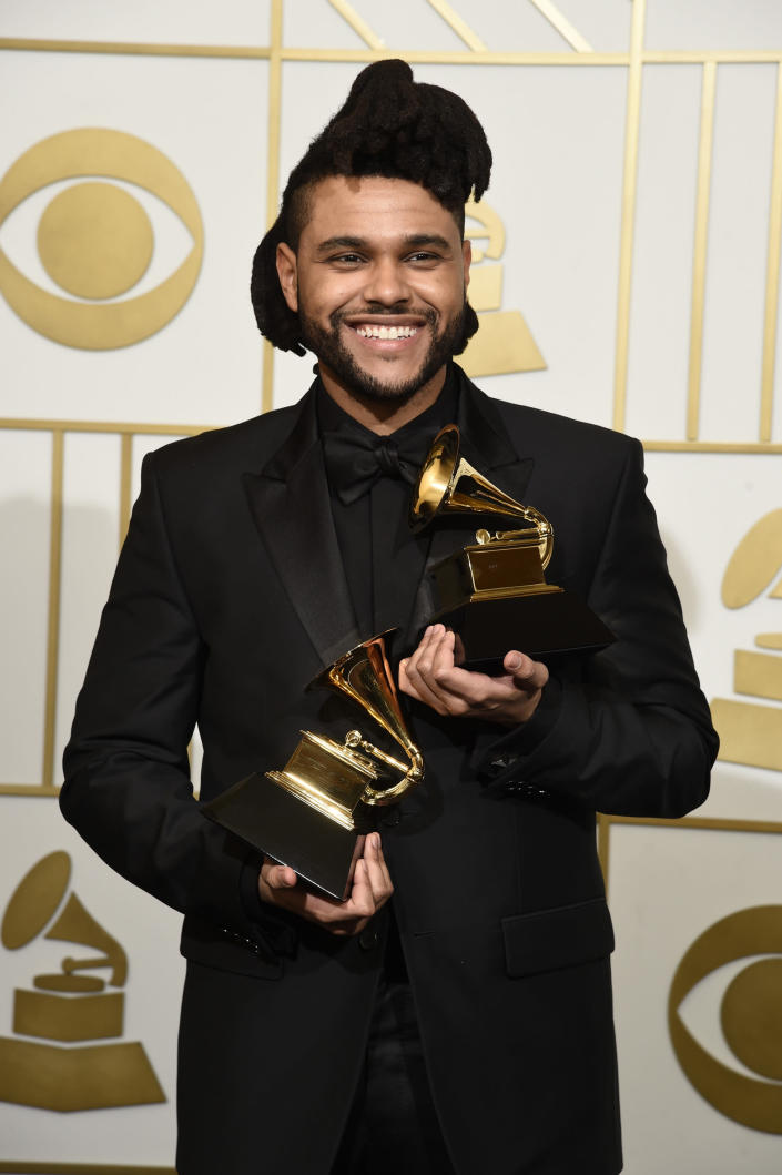"""FILE - The Weeknd poses in the press room with the awards for best R&B performance for """"Earned It (Fifty Shades of Grey)"""" and best urban contemporary album for """"Beauty Behind The Madness"""" at the 58th annual Grammy Awards in Los Angeles on Feb. 15, 2016. The Grammy Awards are in discussion to remove its nomination review committees — the group that determines the contenders for key awards at the coveted music show. (Photo by Chris Pizzello/Invision/AP, File)"""