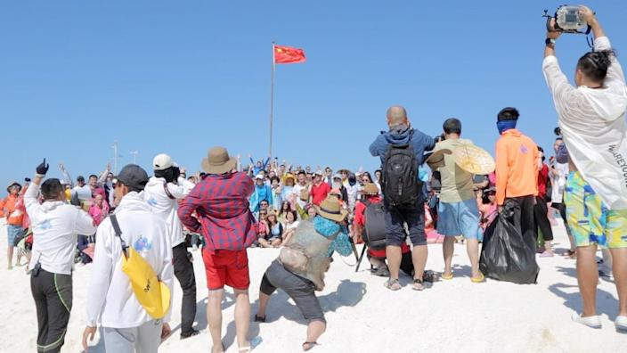 Chinese tourists in front of a Chinese flag on the Paracel Islands