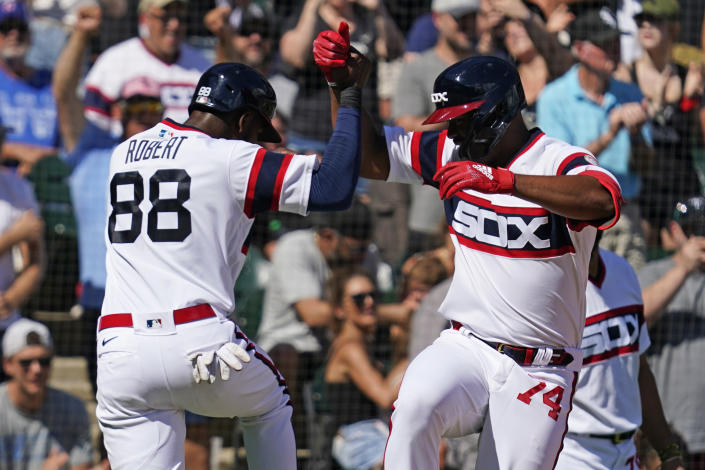 Chicago White Sox's Eloy Jimenez, right, celebrates with Luis Robert after hitting a three-run home run during the fifth inning of a baseball game against the Chicago Cubs in Chicago, Sunday, Aug. 29, 2021. (AP Photo/Nam Y. Huh)