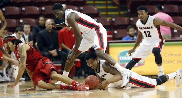 Georgia's Charles Mann, center, hits the floor trying to get to the ball against Nebraska's Terran Petteway, left, while his teammate Brandon Morris stands over him in the first half at the Charleston Classic NCAA college basketball tournament in Charleston, S.C., Sunday, Nov. 24, 2013. In back is Georgia's Kenny Gaines. (AP Photo/Mic Smith)