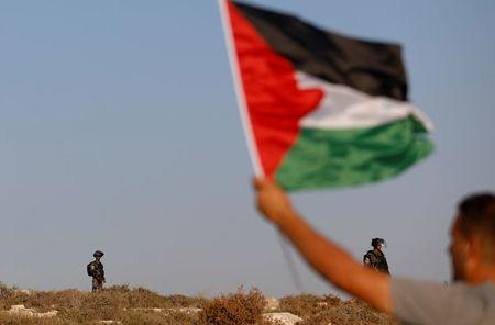 Demonstrator waves a Palestinian flag in front of Israeli border police during a protest near Ramallah in the occupied West Bank