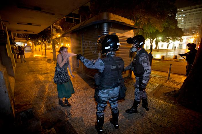 Two Brazilian police officers spray a woman with pepper spray, June 2013.