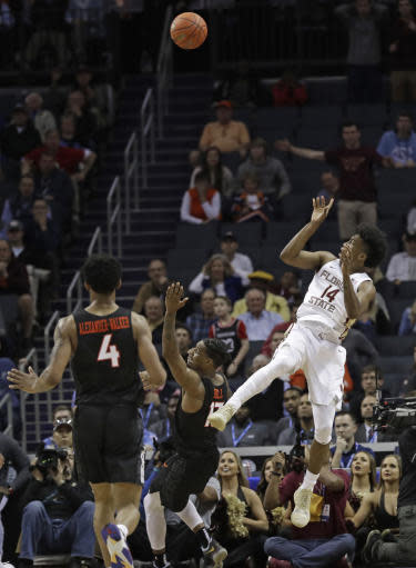 Florida State's Terance Mann (14) shoots the go-ahead and eventual winning basket as Virginia Tech's Ahmed Hill (13) and Nickeil Alexander-Walker (4) watch during overtime of an NCAA college basketball game in the Atlantic Coast Conference tournament in Charlotte, N.C., Thursday, March 14, 2019. (AP Photo/Nell Redmond)