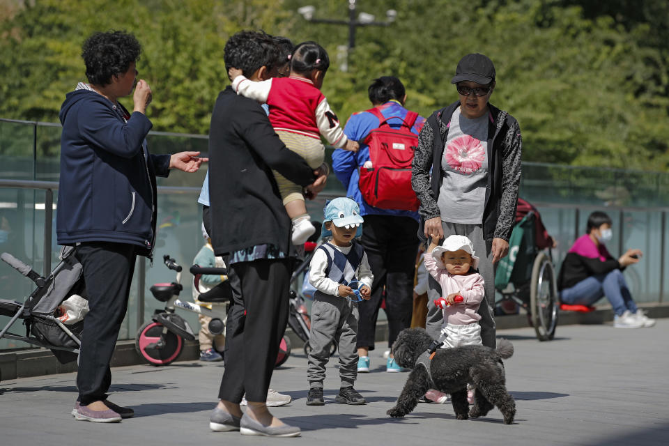 Residents bring their children to play on a compound near a commercial office building in Beijing on Monday, May 10, 2021. China's population growth is falling closer to zero as fewer couples have children, the government announced Tuesday, adding to strains on an aging society with a shrinking workforce. (AP Photo/Andy Wong)
