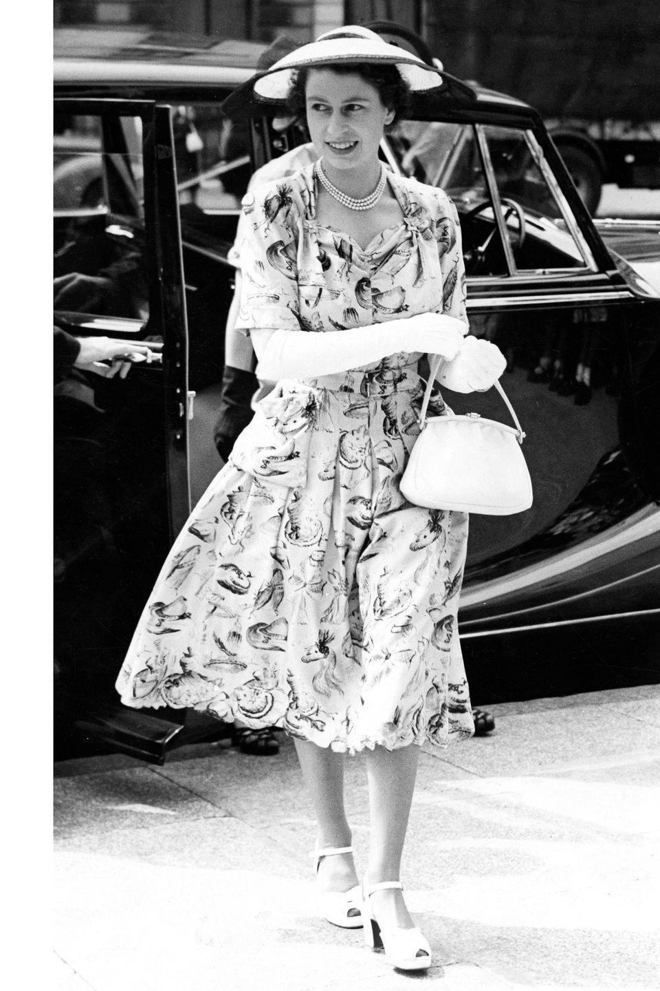 <p>Here she is in a printed knee-length dress, sun hat, white gloves, handle bag, and peep toe heels. </p>