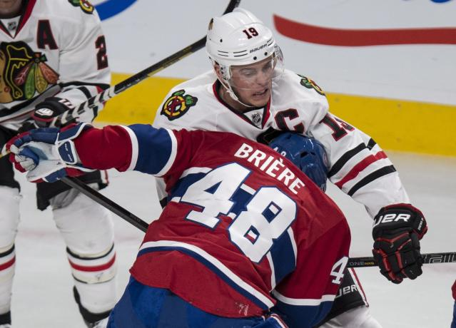 Montreal Canadiens' Daniel Briere digs into Chicago Blackhawks' Jonathan Toews during the first period of an NHL hockey game Saturday, Jan. 11, 2014, in Montreal. (AP Photo/The Canadian Press, Paul Chiasson)