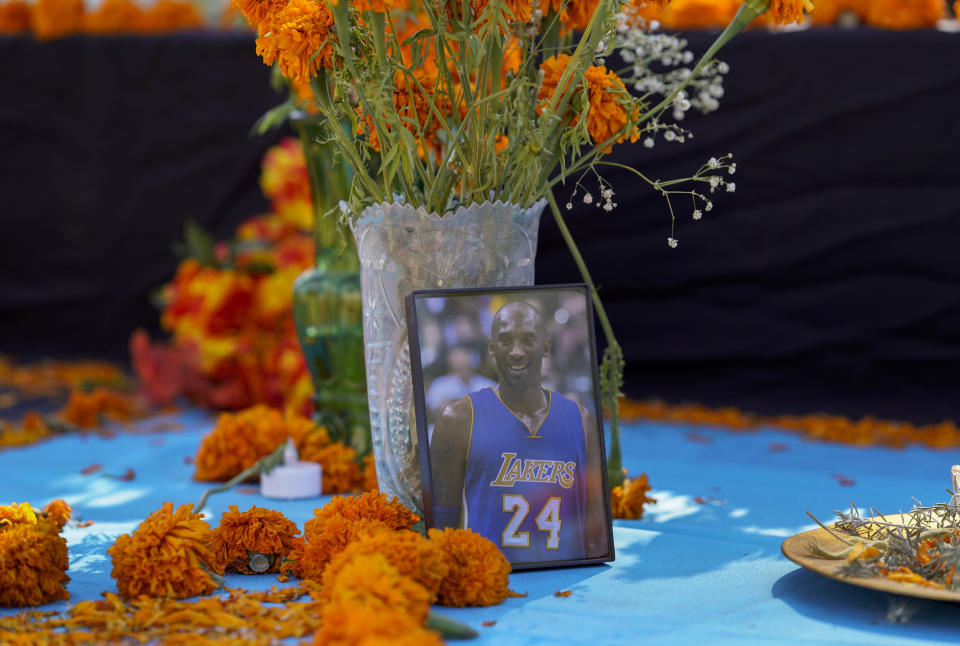 "Fresh marigolds, often called ""flowers of the dead,"" sit next to a picture of late Los Angeles Lakers' basketball player Kobe Bryant left by members of the community, at an altar for Day of the Dead, titled ""2020 Memorial to Our Resilience,"" by artist Ofelia Esparza and her family at Grand Park in Los Angeles, on Thursday, Oct. 29, 2020. (AP Photo/Damian Dovarganes)"