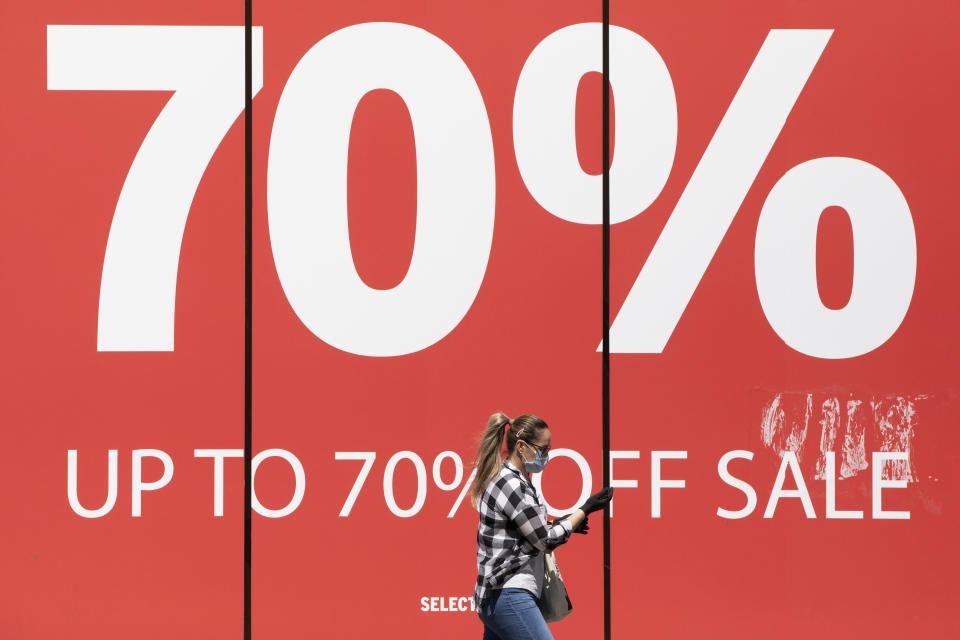 LONDON, ENGLAND  - MAY 19: A woman wearing a face mask walks past a sale sign on Oxford Street on May 19, 2020 in London, England. As shops gear up to open after a long period of closure, clothing stores are beginning to prepare to open their doors, and analysts have suggested that big discounts could be on offer as out of season stock is cleared. The British government has started easing the lockdown it imposed two months ago to curb the spread of Covid-19, abandoning its 'stay at home' slogan in favour of a message to 'be alert', but UK countries have varied in their approaches to relaxing quarantine measures. (Photo by Dan Kitwood/Getty Images)