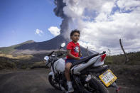 A child sits on a motorcycle as the Pacaya volcano erupts in the background, viewed from San Vicente Pacaya, Guatemala, Wednesday, March 3, 2021. (AP Photo/Santiago Billy )