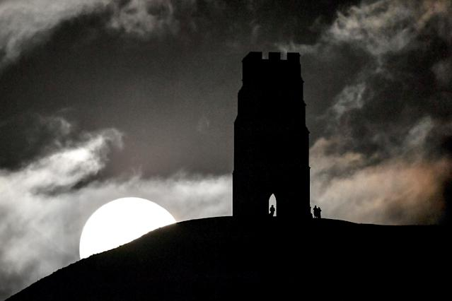 <p>A Blue Moon rises behind Glastonbury Tor, Somerset. (Photo: Ben Birchall/PA Images via Getty Images) </p>