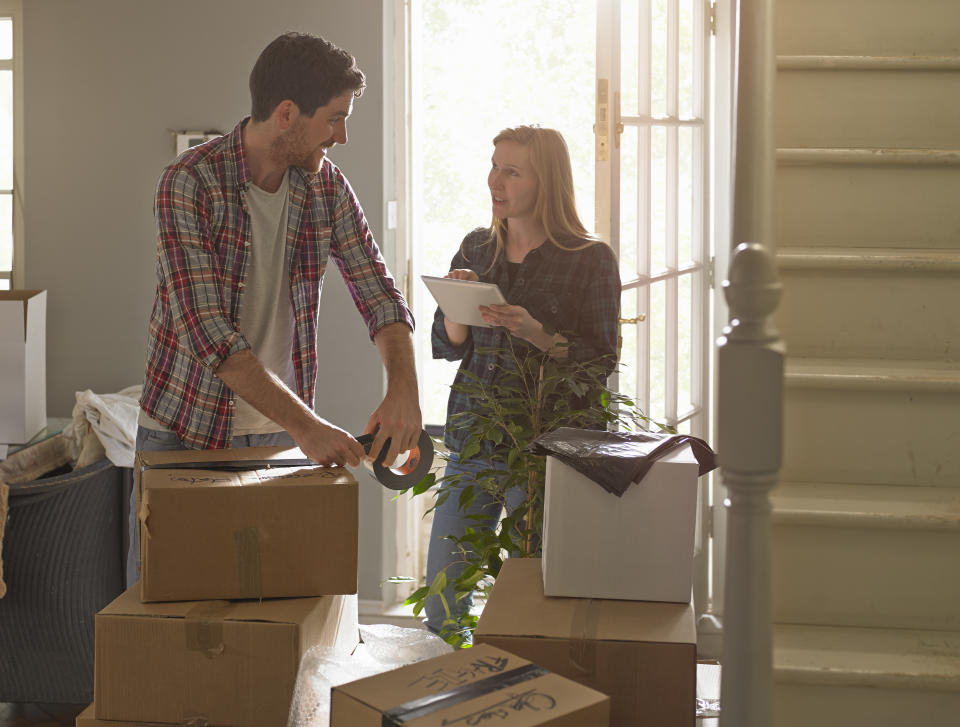 Young professional couple are moving home they have a checklist on tablet computer.