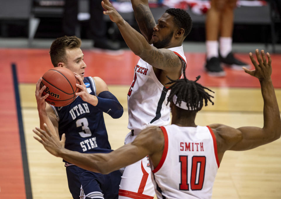 Utah State guard Steven Ashworth (3), left, is trapped along the baseline by Texas Tech guard Jamarius Burton (2) and forward Tyreek Smith (10) during the first half of a first round game in the NCAA men's college basketball tournament, Friday, March 19, 2021, in Bloomington, Ind. (AP Photo/Doug McSchooler)
