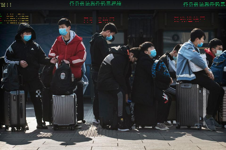 People wearing masks with their suitcases.