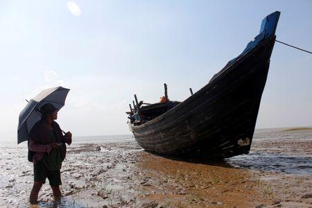 A stranded boat which was used by Rohingya Muslims is seen at the Thande village beach outside Yangon