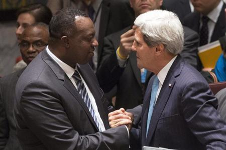 Rwanda Ambassador to the United Nations Eugene-Richard Gasana greets U.S. Secretary of State John Kerry after taking part in a United Nations Security Council meeting in New York