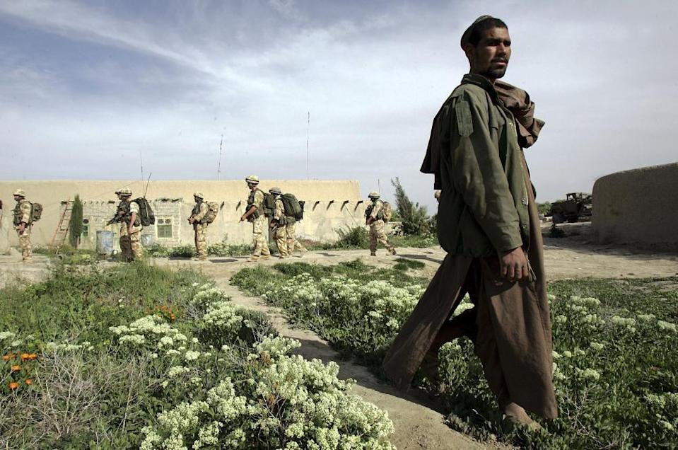 British soldiers passing a farmer in Musa Qala, March 2006