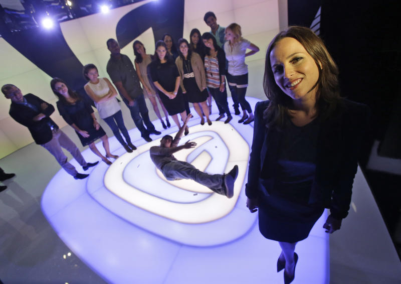 """In this Monday, Oct. 14, 2013 photo Alicia Menendez, right, host of the """"Alicia Menendez Tonight"""" show on Fusion, an English-language television network targeting millennial Hispanics, poses with her production team at the network's studio in Doral, Fla. Menedez describes her new Fusion show as a mix of sex, money and politics. (AP Photo/Wilfredo Lee)"""