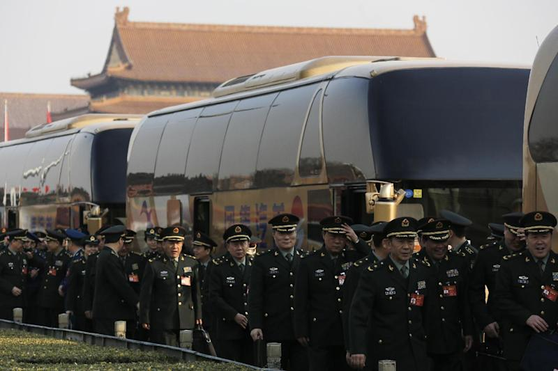 Delegates from China's People's Liberation Army (PLA) arrive at the Great Hall of the People to attend a plenary session of the National People's Congress in Beijing, Saturday, March 4, 2017. China will raise its defense budget by about 7 percent this year, a government spokeswoman said Saturday, continuing a trend of lowered growth amid a slowing economy. (AP Photo/Andy Wong)
