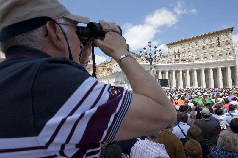A man looks through a binocular as Pope Francis blesses the crowd during the Angelus noon prayer, from the window of his studio overlooking St. Peter's Square, at the Vatican, Sunday, June 2, 2013. (AP Photo/Andrew Medichini)