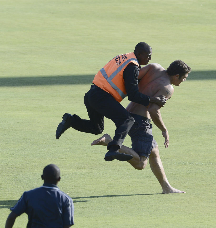 Stadium security  tries to stop a man  running on the pitch during the third day of the third Test match between South Africa and Pakistan on February 24, 2013 at Super Sport Park in Centurion. AFP PHOTO / STEPHANE DE SAKUTIN        (Photo credit should read STEPHANE DE SAKUTIN/AFP/Getty Images)