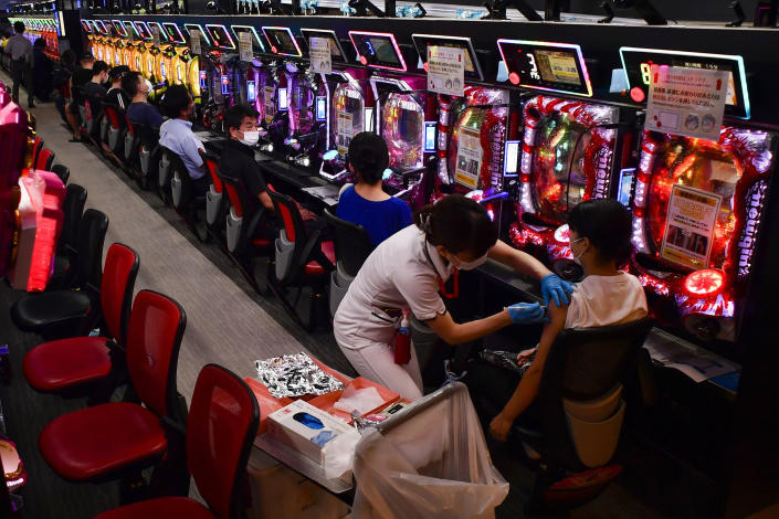 A woman receives the first shot of the Moderna COVID-19 vaccine as others wait for their turn in front of pachinko pinball machines at the pachinko parlor Freedom in Osaka, western Japan, Monday, Sept. 13, 2021. A nearby hospital dispatched medical workers to administer the vaccine to 1,500 people in two days at the pinball parlor which became a makeshift vaccination site. (Kyodo News via AP)