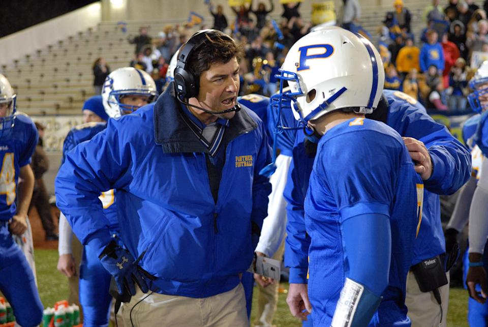 Kyle Chandler yells at Zach Gilford on the sidelines of a football field