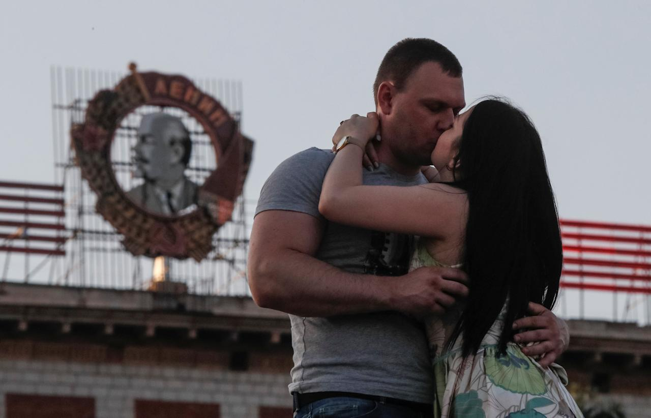 A couple kiss in front of a residential building with the Soviet Order of Lenin seen on top, in Volgograd, Russia, August 21, 2017.  REUTERS/Maxim Shemetov