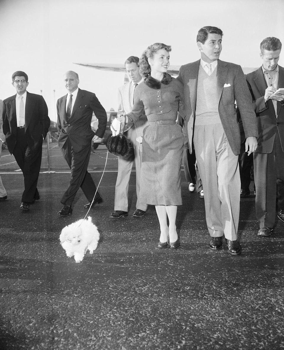 <p>Pictured at the beginning of their romance, Debbie Reynolds arrives at the airport to meet crooner, Eddie Fisher, with her latest token of affection: their white Poodle puppy named Fanny Fisher. The couple got married later that year. </p>