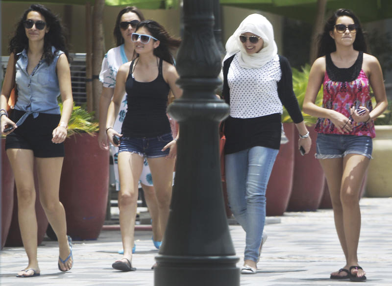In this photo taken Saturday, June 23, 2012, Women of different nationalities walk at the Jumeirah Beach Residence Walk in Dubai , United Arab Emirates. As the numbers of foreigners have increased, so have the stories of them violating the UAE's strict indecency code which limits drinking to bars and nightclubs and bans public displays of affection. (AP Photo/Kamran Jebreili)