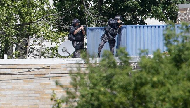 Armed police officers on the roof of the Sikh temple in Oak Creek, Wis. (Photo: Jeffrey Phelps/Associated Press)