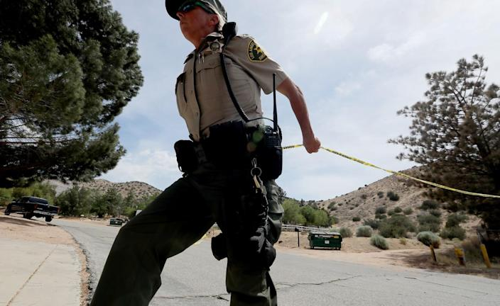 A deputy stretches police tape across a street surrounded by low, scrub-covered hills.