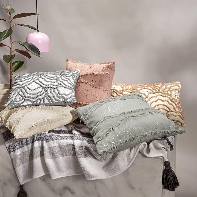 "The <a href=""https://fave.co/2TgGZNe""><strong>Pom Pom</strong></a> and <a href=""https://fave.co/2GsZkPh""><strong>Fringe Cushion Covers by The Label Life</strong></a>. Cotton with velvet and silver foil detailing Size: 11.5 X 19.5 inches (Pom Pom), 18 X 18 inches (Fringe). <em>Rs.594 each, on offer.</em> <a href=""https://fave.co/2GsZkPh""><strong>Buy here!</strong></a>"