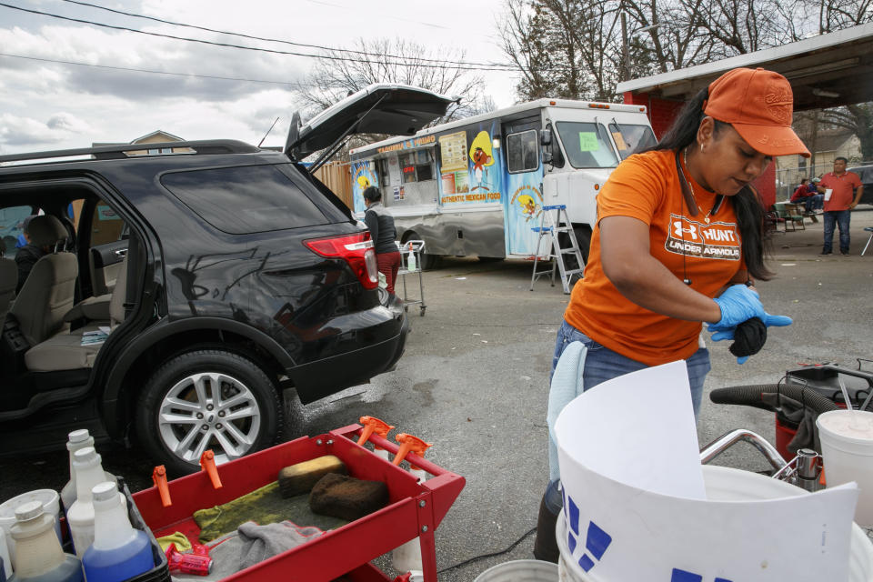 Esperanza Carrillo, of Burlington, N.C., washes cars at Vivas Hand Car Wash, Wednesday, March 11, 2020, along a strip of Latino owned businesses. (AP Photo/Jacquelyn Martin)