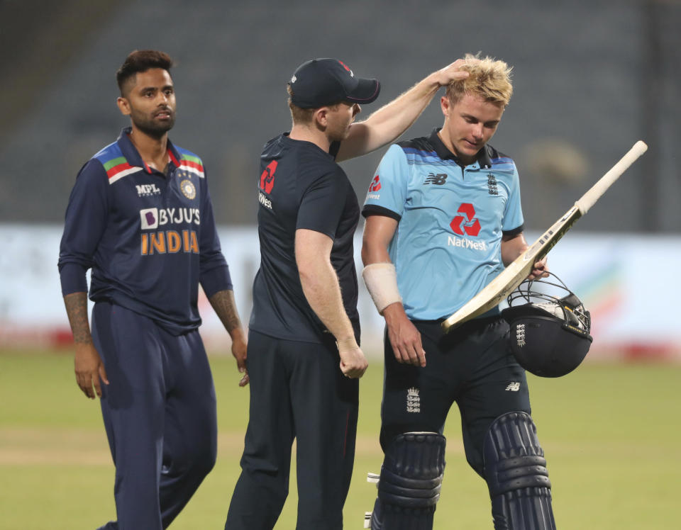 England's Eoin Morgan, center, pats teammate Sam Curran as he walks off the field after their loss in the third One Day International cricket match between India and England at Maharashtra Cricket Association Stadium in Pune, India, Sunday, March 28, 2021. India Won the series 2-1. (AP Photo/Rafiq Maqbool)