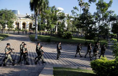 Military personnel walk outside the Paraguayan Congress building where lawmakers argue over a possible change in law that would allow President Horacio Cartes to run for re-election, in Asuncion, Paraguay March 28, 2017. REUTERS/Jorge Adorno