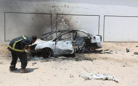 A firefighter attempts to extinguish a burning car after a clash among gunmen and security members in Madina district of Somalia's capital Mogadishu, April 16, 2017. REUTERS/Feisal Omar
