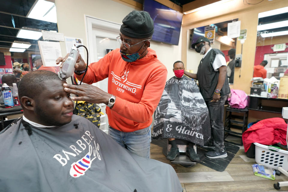 Kevin Fitzhugh, center left, cuts the hair of Mabreco Wright, left, as Wallace Wilson, right, cuts the hair of James McRae, Friday, April 9, 2021, in Hyattsville, Md. Barbers such as Fitzhugh and Wilson are members of the Health Advocates In Reach & Research (HAIR) program, which helps barbers and hair stylists to get certified to talk to community members about health. During the COVID-19 pandemic, a team of certified barbers have been providing factual information to customers about vaccines, a topic that historically has not been trusted by members of black communities because of the health abuse the race has endured over the years. (AP Photo/Julio Cortez)