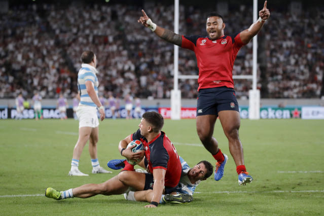 CORRECTS NAME: Manu Tuilagi, right, celebrates after teammate Ben Youngs, left, after he scored a try against Argentina during the Rugby World Cup Pool C game at Tokyo Stadium in Tokyo, Japan, Saturday, Oct. 5, 2019. (AP Photo/Christophe Ena)