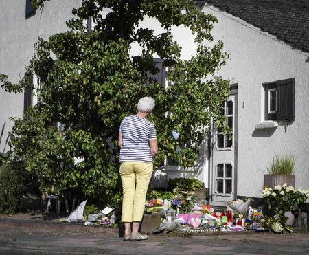 A woman looks at flowers placed in front of the house of a family who were all killed in Thursday's Malaysia Airlines Boeing 777 plane crash, in Neerkant, near Eindhoven July 19, 2014. REUTERS/Mischa Rapmund
