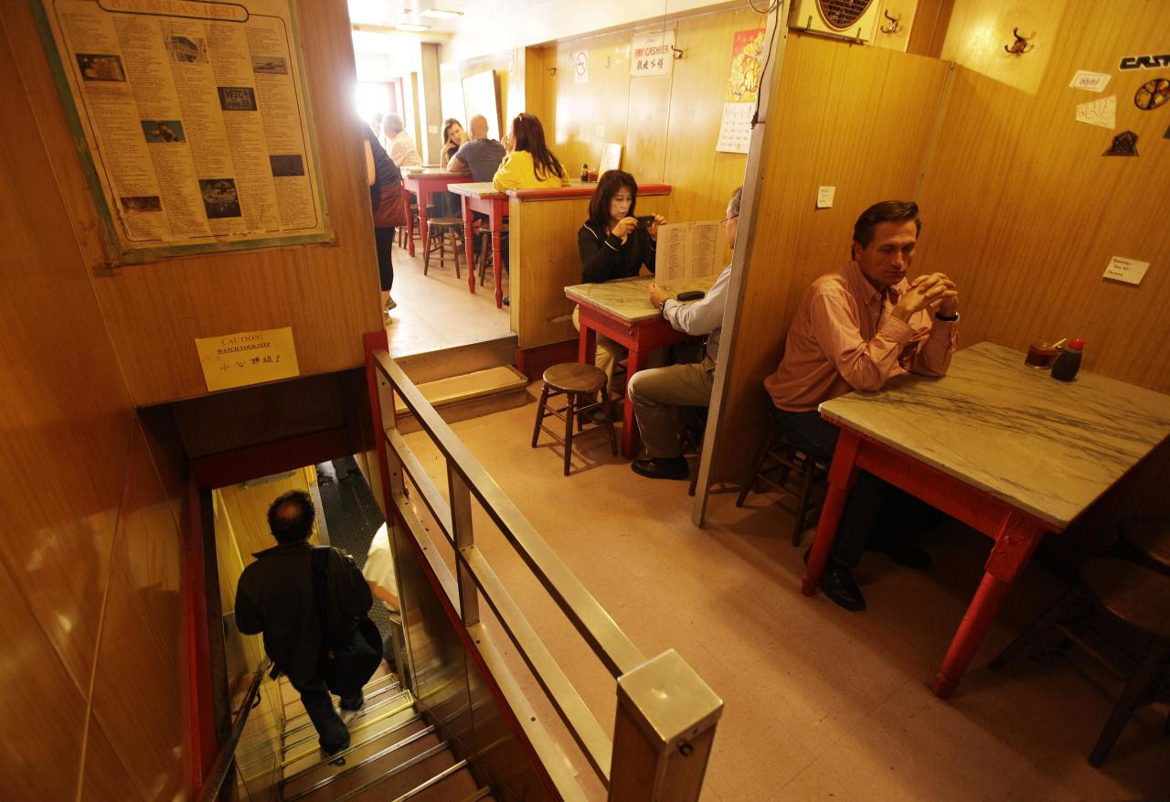 """A customer makes his way down a tiny stairway during lunch at the Sam Wo restaurant in Chinatown in San Francisco, Friday, April 20, 2012. The 100-year-old Chinese restaurant known for having """"the world's rudest waiter"""" is shutting its doors and serving its last customers Friday. (AP Photo/Eric Risberg)"""