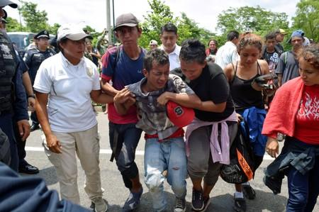 Migrants help a fellow migrant, who got injured during a joint operation by the Mexican government to stop a caravan of Central American migrants on their way to the U.S., at Metapa de Dominguez